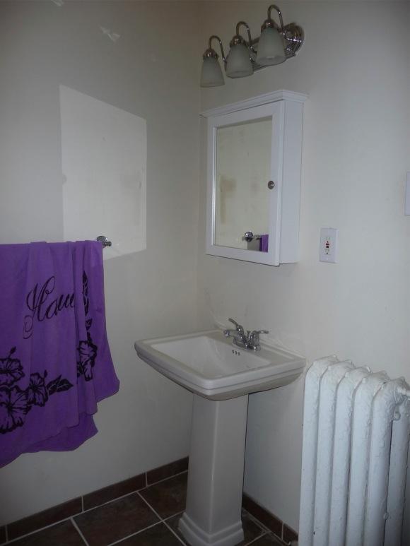 Bathroom from in front of toilet, door is to right of radiator